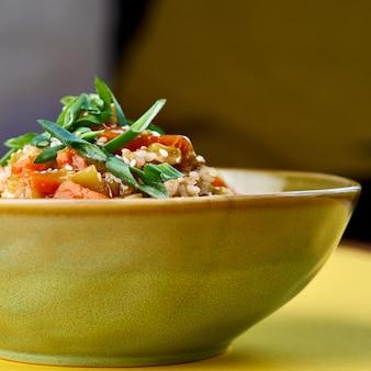 Schüssel mit gebratenem reis und gemüse. traditionelles chinesisches essen. horizontale ansicht auf gelb