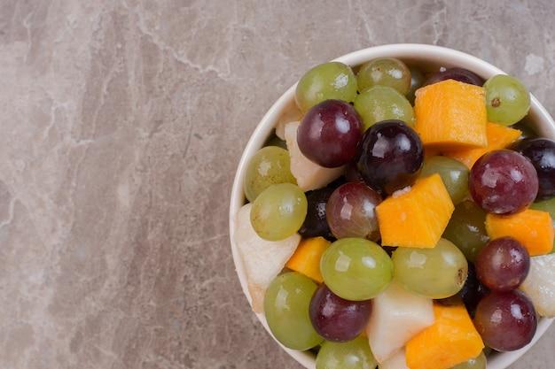 Schüssel mit gemischten früchten auf marmoroberfläche.