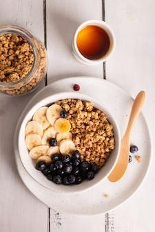 Schüssel mit gesundem müsli mit honig, banane und beeren zum frühstück