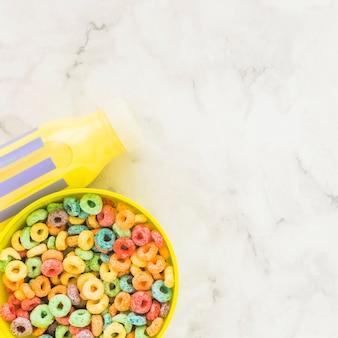 Schüssel mit getreide und gelber milchflasche