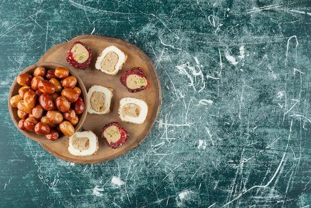 Schüssel mit getrockneten datteln und süßen köstlichkeiten auf holzstück.