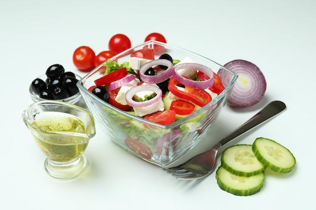 Schüssel mit griechischem salat und zutaten auf weiß