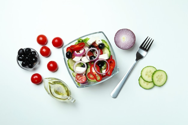 Schüssel mit griechischem salat und zutaten auf weißem hintergrund