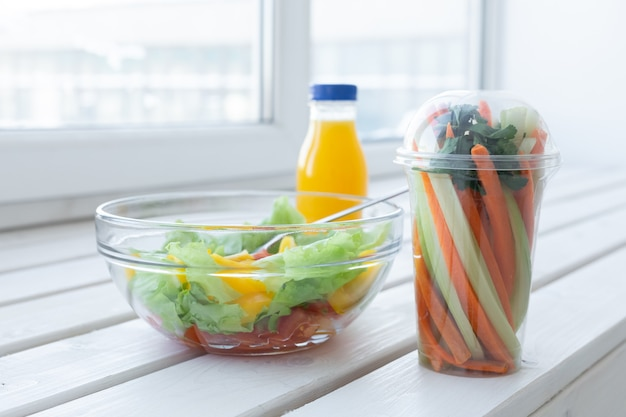 Schüssel mit grünem salat, rohem gemüse und einer flasche orangensaft. gewichtsverlust, diät und richtiges ernährungskonzept