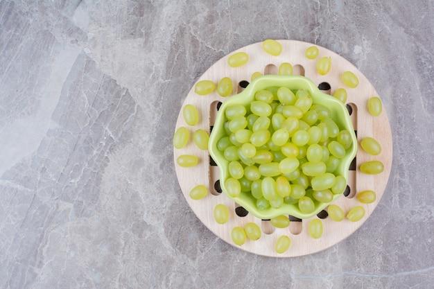 Schüssel mit grünen trauben auf holzstück.