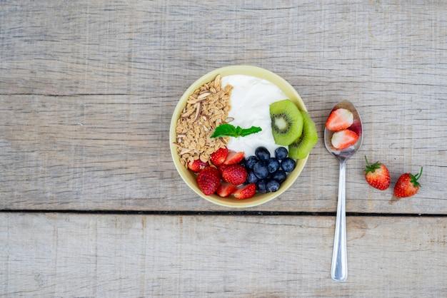 Schüssel mit hausgemachtem müsli mit frischem natürlichem selbstgemachten bio-joghurt, beeren, erdbeeren, kiwis