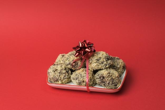 Schüssel mit hausgemachten keksen gebunden mit einem roten band auf einem roten hintergrund. leckere frische hausgemachte süßigkeiten.