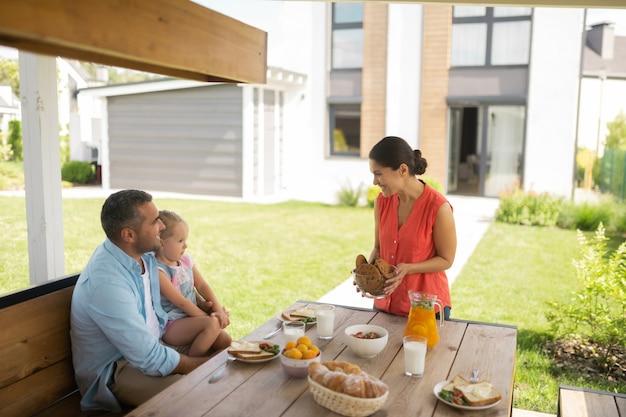 Schüssel mit keksen. liebevolle schöne mutter, die eine schüssel mit keksen bringt, während sie draußen frühstückt?
