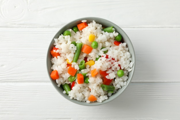 Schüssel mit köstlichem reis mit gemüse auf holzoberfläche