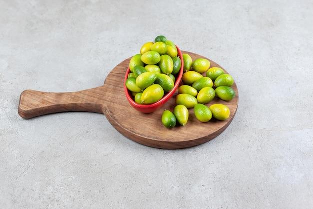 Schüssel mit kumquats neben einem stapel auf einem holzbrett in marmoroberfläche.
