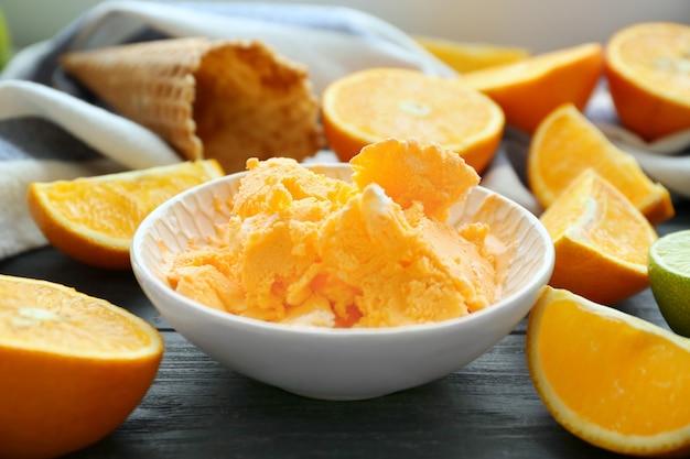 Schüssel mit leckerem eis und orangen auf holztisch