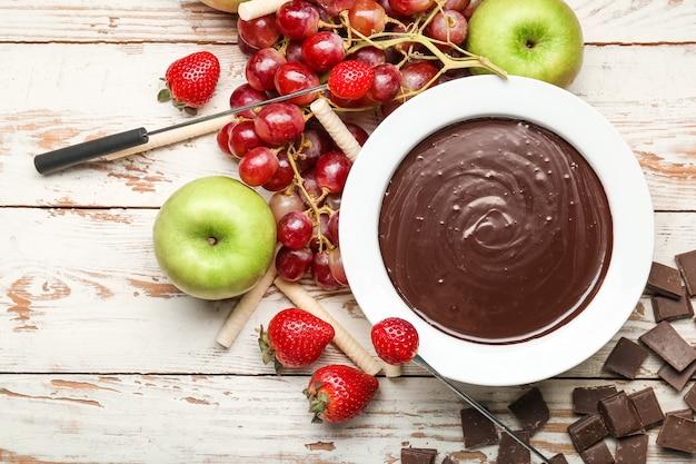 Schüssel mit leckerem schokoladenfondue und früchten auf dem tisch