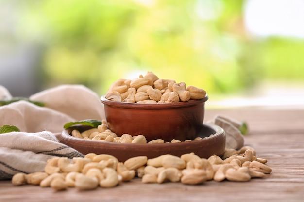 Schüssel mit leckeren cashewnüssen auf holztisch gegen unschärfe