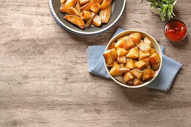 Schüssel mit leckeren kartoffelecken auf dem tisch