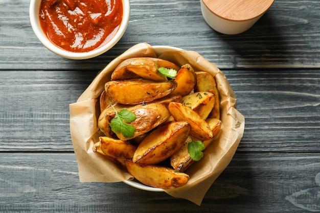 Schüssel mit leckeren kartoffelecken und tomatensauce auf dem tisch