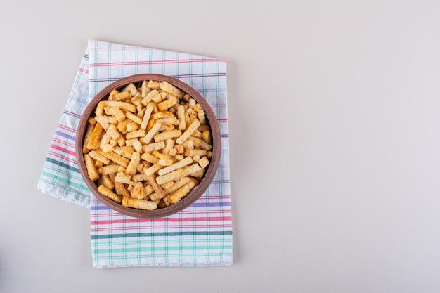 Schüssel mit leckeren knusprigen crackern mit tischdecke auf marmorhintergrund. foto in hoher qualität