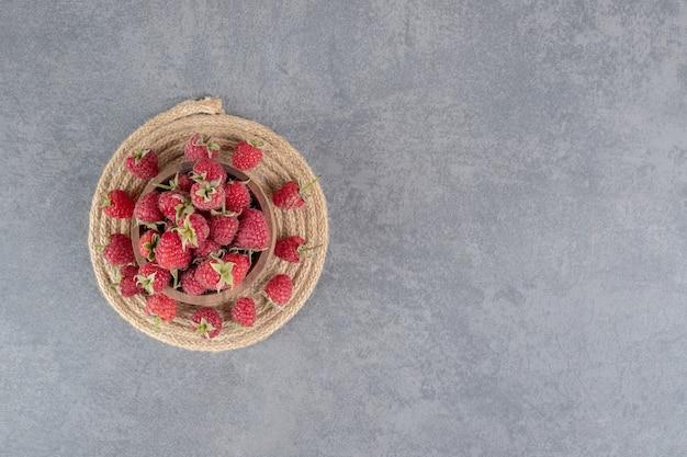 Schüssel mit leckeren roten himbeeren auf marmorhintergrund. foto in hoher qualität