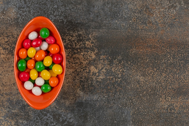 Schüssel mit leckeren süßigkeiten auf marmor.