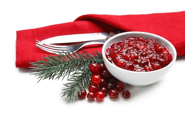 Schüssel mit leckerer cranberry-sauce und besteck auf weiß