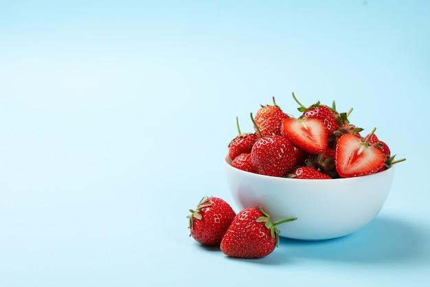 Schüssel mit leckerer erdbeere auf blauem hintergrund