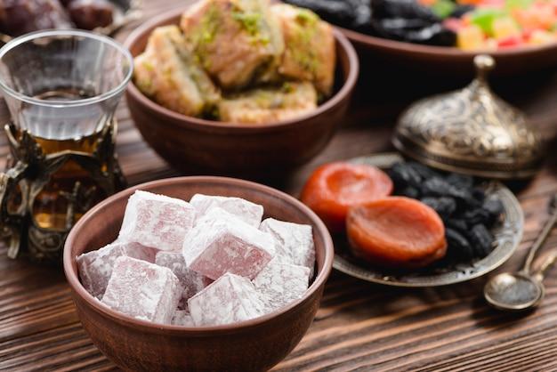 Schüssel mit lukum; tee und trockenfrüchte auf dem tisch