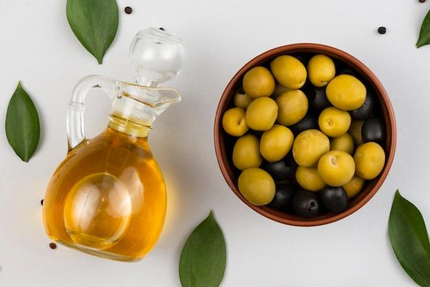 Schüssel mit oliven und olivenölflasche