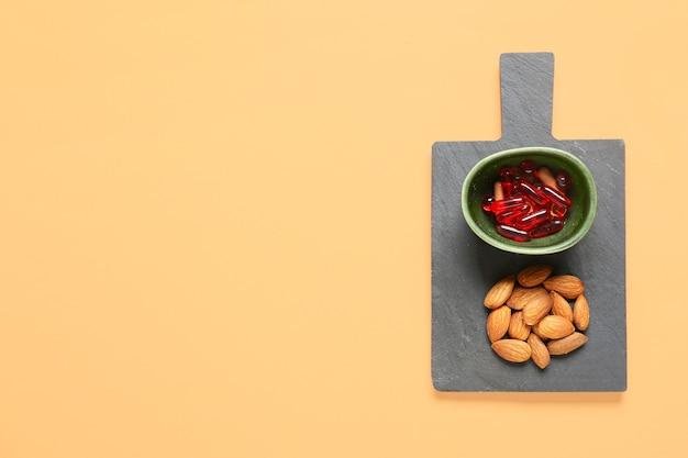 Schüssel mit pillen und mandelnüssen auf der farboberfläche