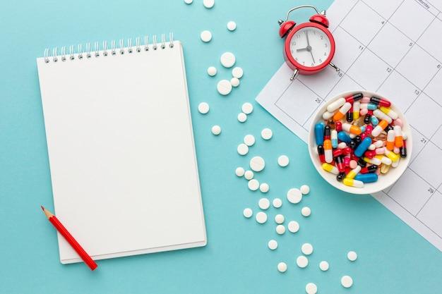 Schüssel mit pillen und uhr daneben auf dem schreibtisch