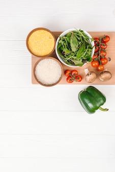 Schüssel mit polenta; reiskörner; blattgemüse; pilz; kirschtomaten und grüner pfeffer auf weißer planke
