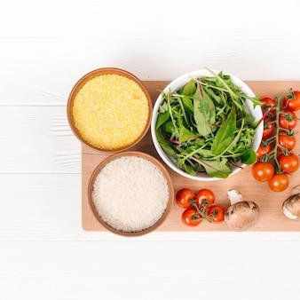 Schüssel mit polenta; reiskörner; mangold; pilz- und kirschtomaten auf schneidebrett über der weißen planke