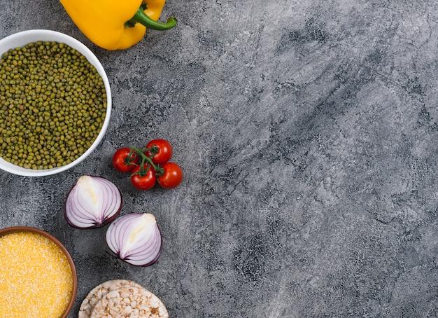 Schüssel mit polenta und mungobohnen; zwiebel; kirschtomaten; zwiebel- und puffreiskuchen auf grauem konkretem hintergrund