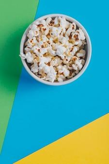 Schüssel mit popcorn auf buntem hintergrund. genres des konzeptfilms. filmgenres: komödie, fantasy, kinderfilm und dokumentarfilm