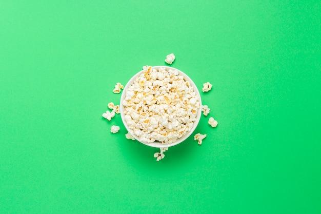 Schüssel mit popcorn auf einem grünen hintergrund. flache lage, draufsicht.
