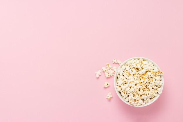 Schüssel mit popcorn auf einem rosa hintergrund. flache lage, draufsicht.