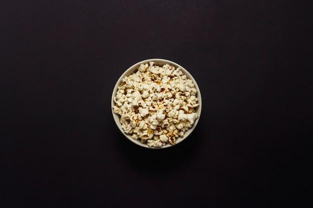 Schüssel mit popcorn auf einem schwarzen hintergrund. flache lage, draufsicht.