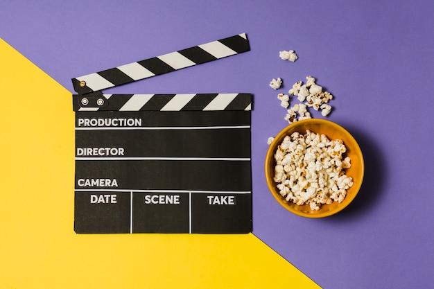 Schüssel mit popcorn neben filmschiefer
