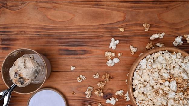 Schüssel mit popcorn und eis auf holzuntergrund.