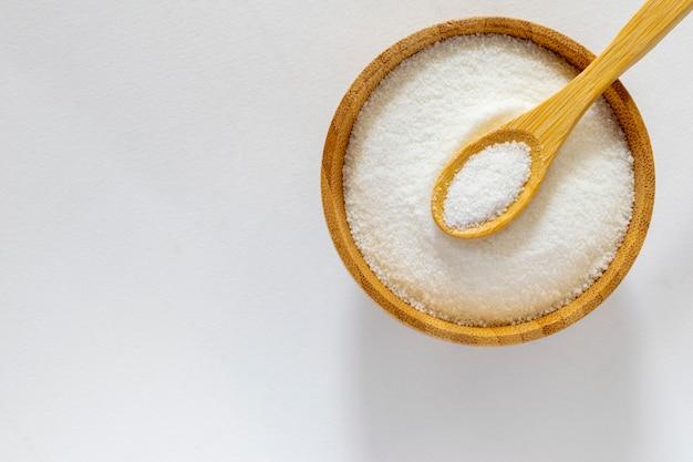 Schüssel mit raffiniertem zucker auf einem weißen tisch. ansicht von oben