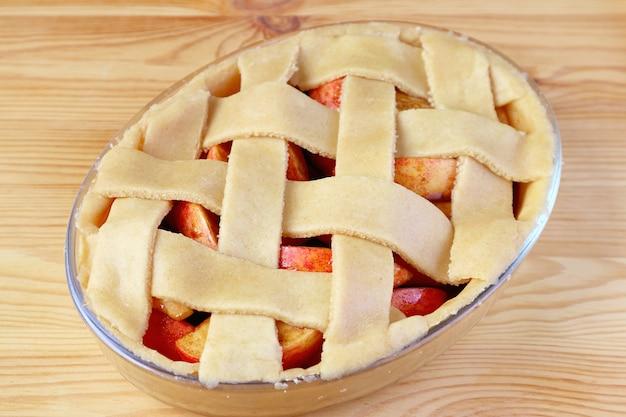 Schüssel mit rohem apfelkuchen mit dekorativer, gewebter gitterkruste, die zum backen bereit ist