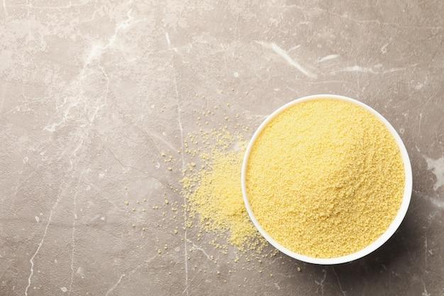Schüssel mit rohem couscous auf grauem hintergrund
