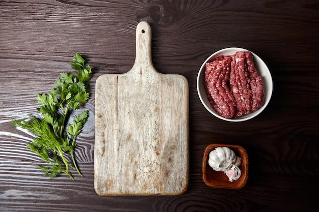 Schüssel mit rohem rinderhackfleisch und gewürzen knoblauch und gemüse