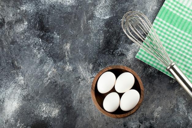 Schüssel mit rohen eiern und schnurrbart auf marmoroberfläche.