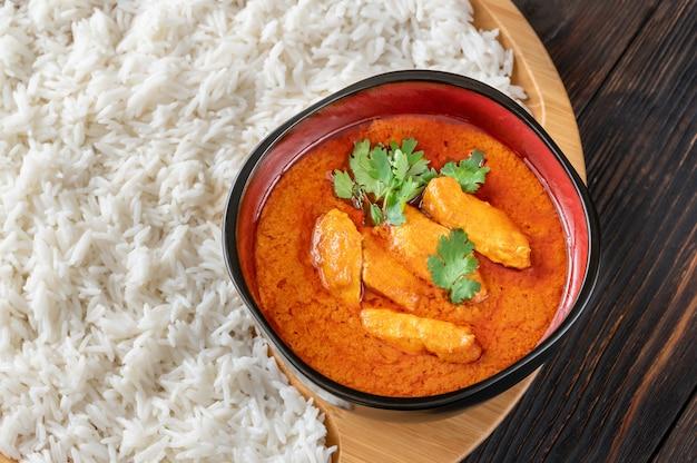 Schüssel mit rotem thai-hähnchen-curry, garniert mit weißem reis