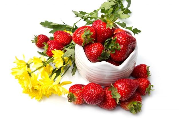 Schüssel mit roter erdbeere und blume