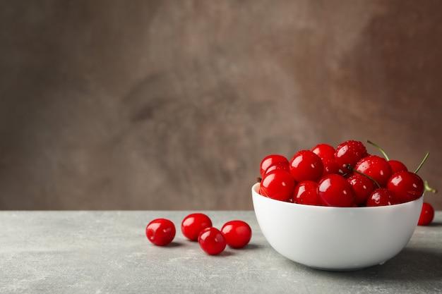 Schüssel mit roter kirsche auf grauem tisch, platz für text