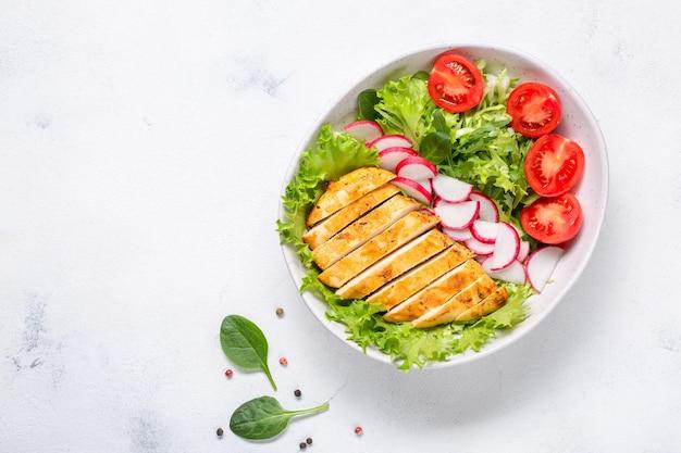 Schüssel mit salat und in scheiben geschnittenem hühnerfilet. diät-mittagessen, keto-diät, gesundes essen. ansicht von oben.