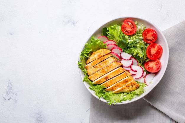 Schüssel mit salat und in scheiben geschnittenem hühnerfilet. diät-mittagessen, keto-diät, gesundes essen. draufsicht auf weißem hintergrund.