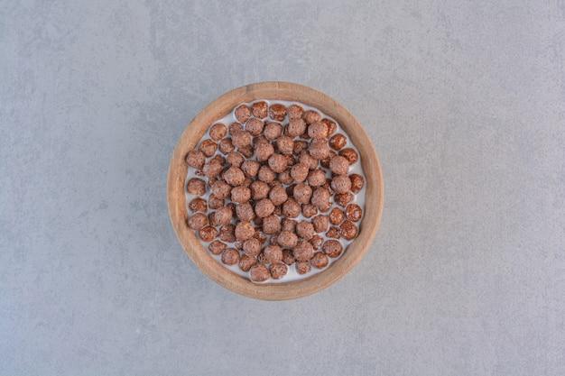 Schüssel mit schokoladen-müslikugeln mit milch auf stein.