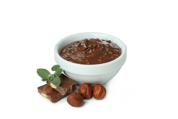Schüssel mit schokoladenpaste und nüssen auf weißem hintergrund