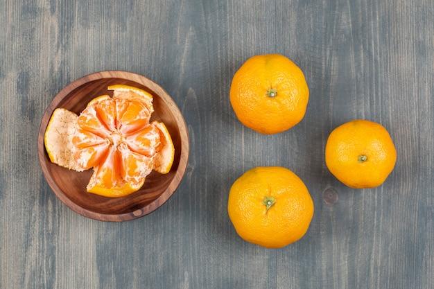 Schüssel mit segmenten mit ganzen mandarinen auf marmoroberfläche